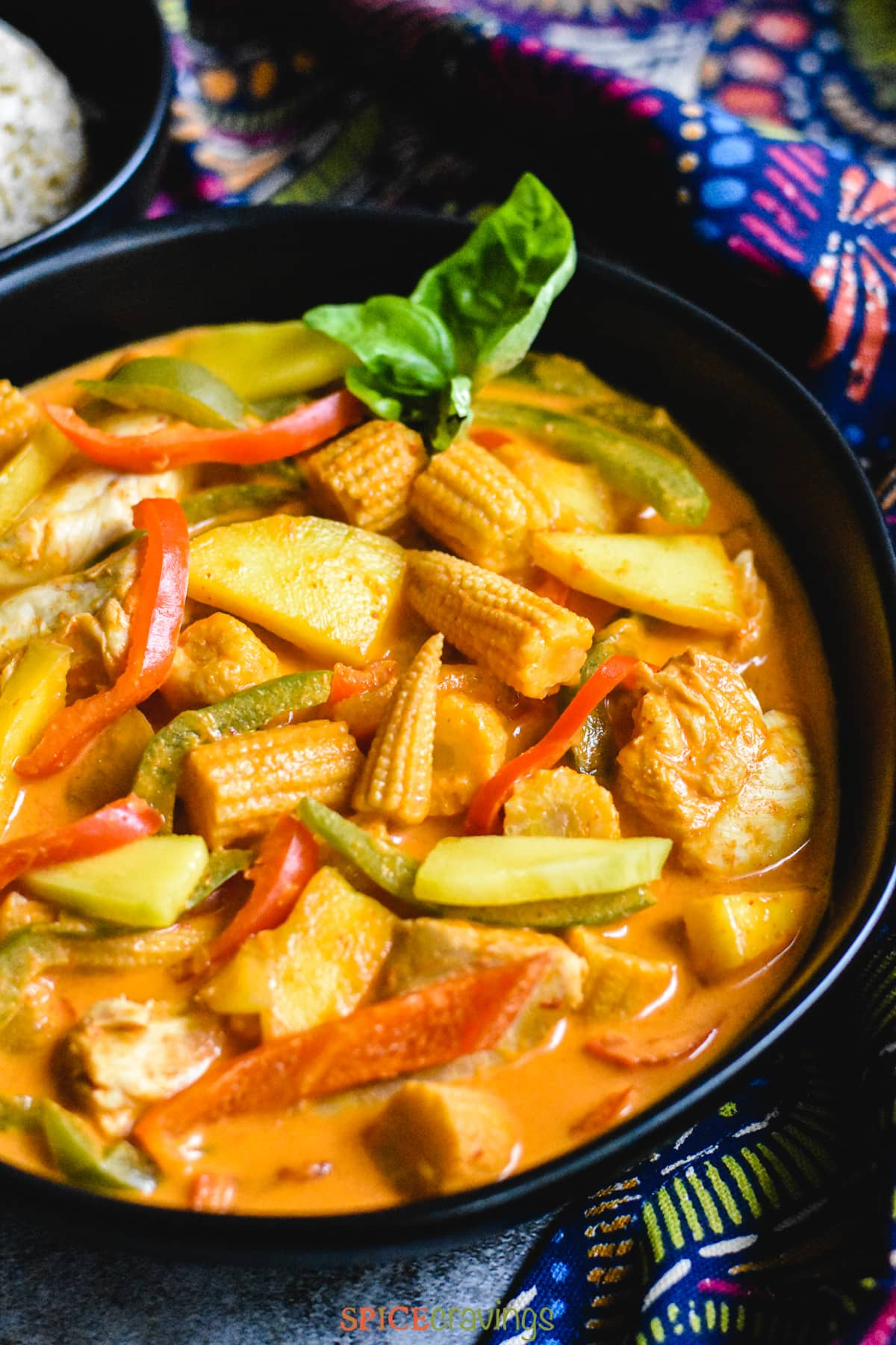 close-up of mango chicken curry in black bowl
