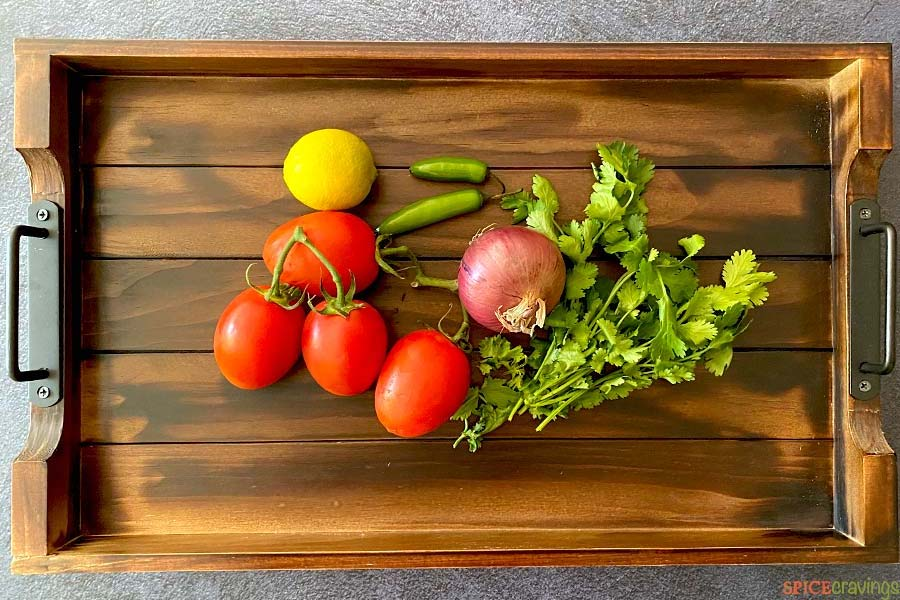 A wooden tray with tomatoes, onion, cilantro, lime and chili