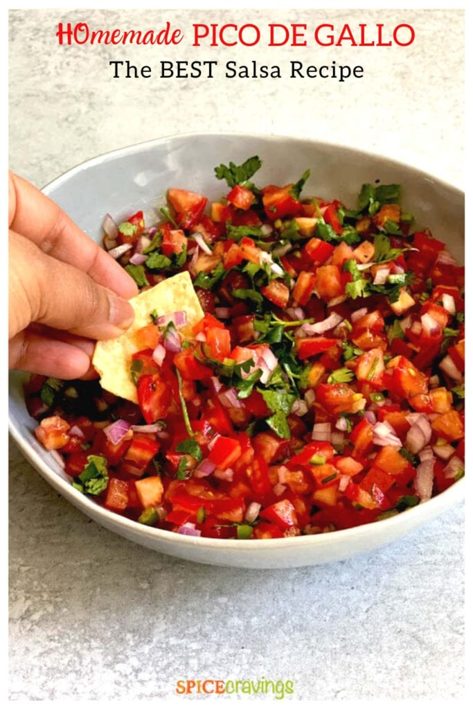 Hand dipping tortilla chip in a bowl of salsa