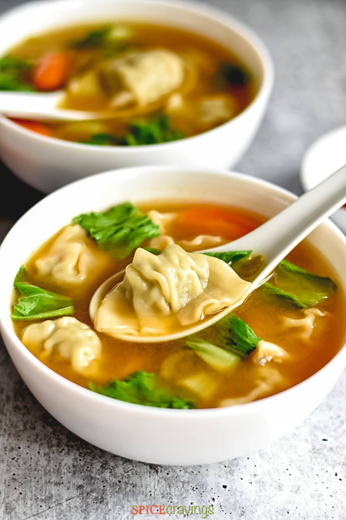Two bowls of soup with dumplings, spinach and carrots