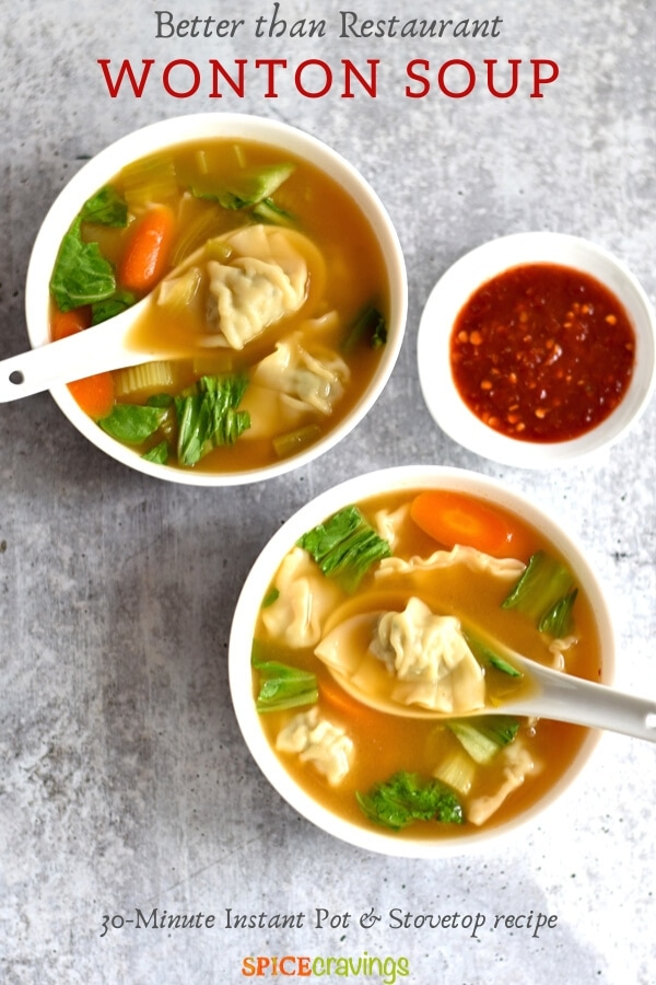 Two bowls of wonton soup with chili sauce next to it