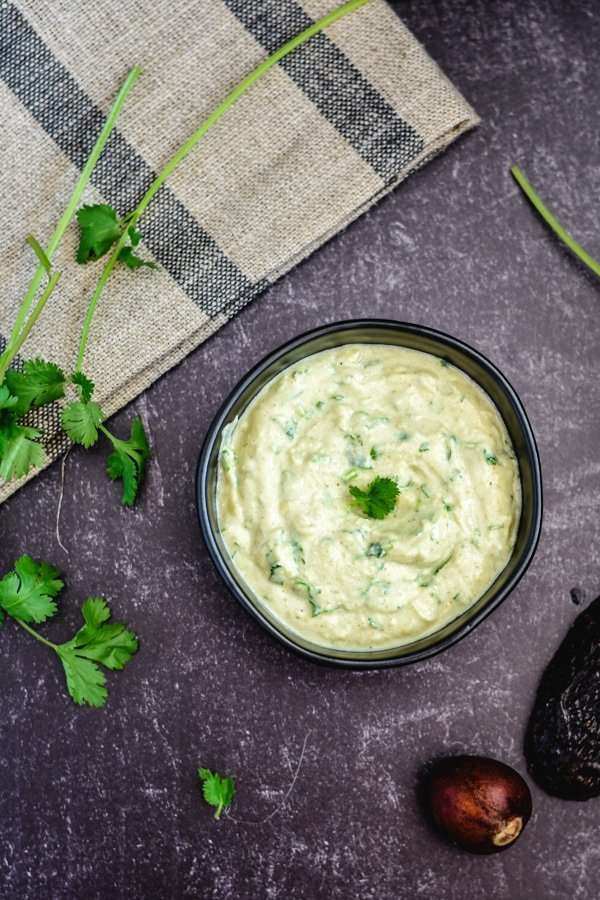 avocado yogurt dip garnished with cilantro in black bowl