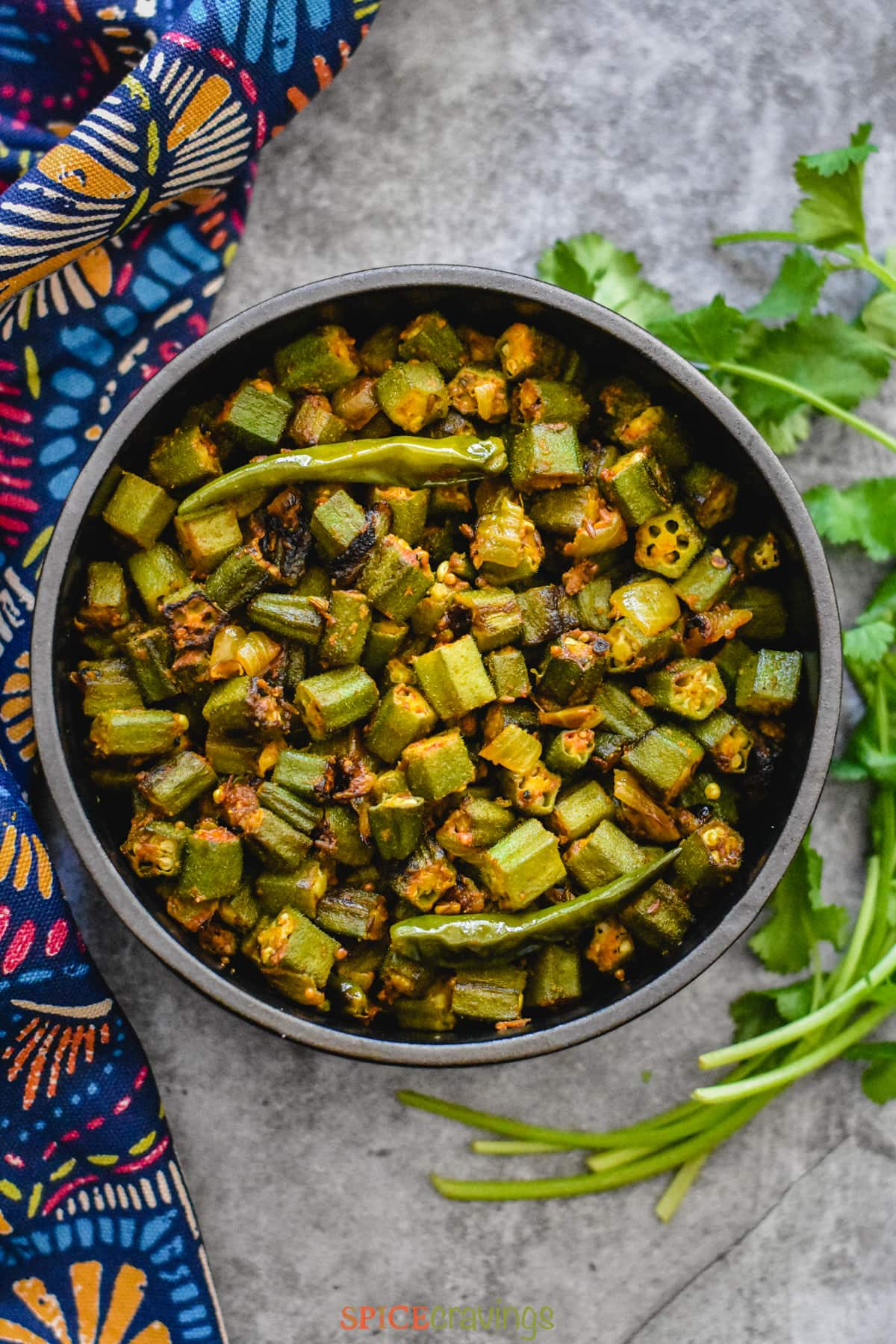 chopped okra, chile, onions and spices in black bowl