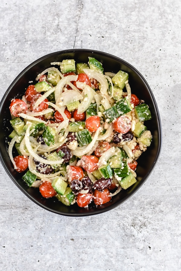chopped cucumbers, tomatoes, onions, olives, feta with lemon dressing in black bowl