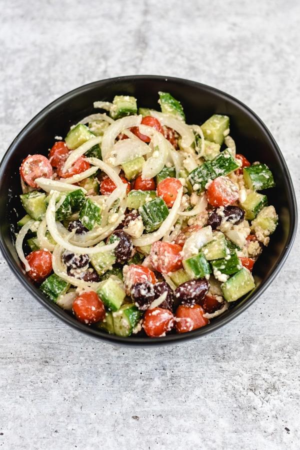 chopped cucumbers, tomatoes, onions, olives, feta in black bowl