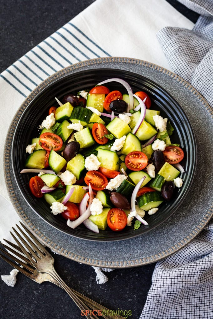 Bowl with halved tomatoes, cucumber, red onions and feta cheese crumbles