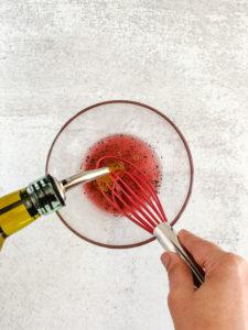 two hands whisking lemon dressing in glass bowl