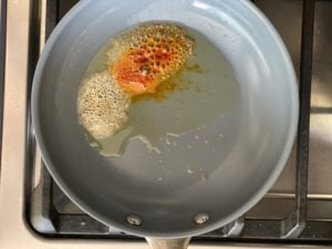 Preparing tadka by tempering ghee and spices