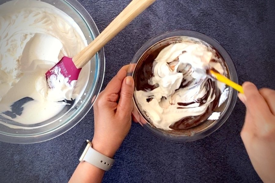 two hands mixing whipped cream into chocolate with spatula