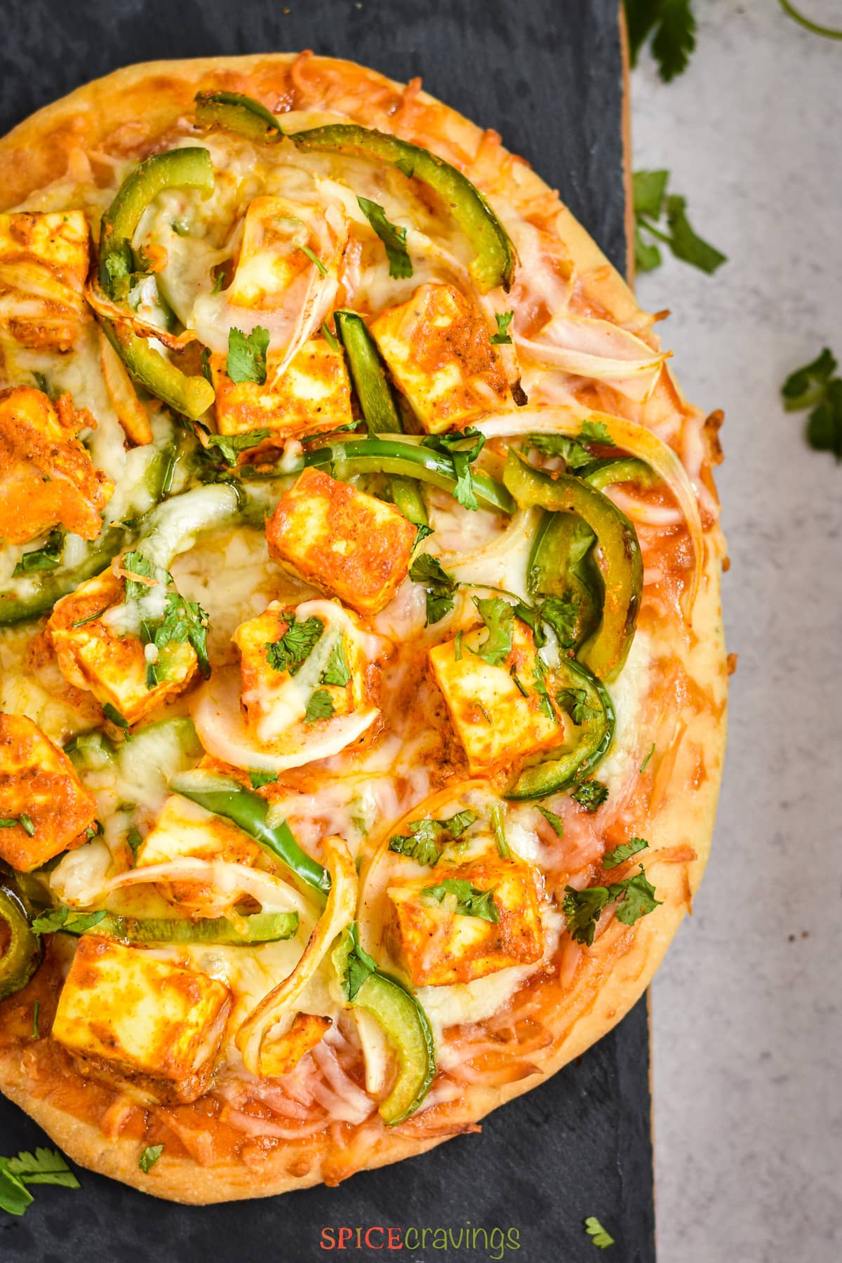 slices of indian flatbread pizza with marinated paneer cheese and veggies on black board