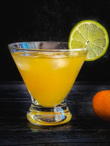 An orange cocktail garnished with a lime wheel