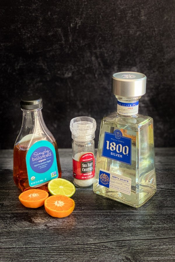 Ingredients for making skinny margarita, includingTequila, agave, salt, lime and orange on a gray board