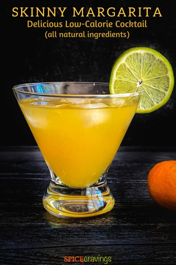 An orange drink in a glass decorated with a lime wheel