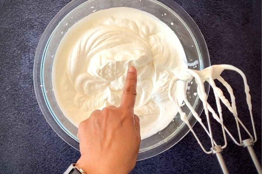 hand pointing at soft peaks of cream in glass bowl