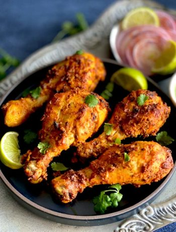 Grilled Tandoori Chicken legs placed on a metal platter