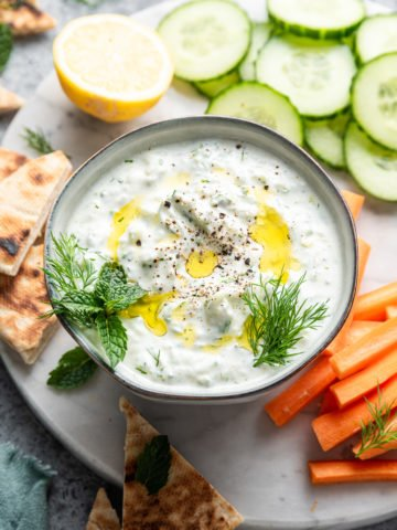 Greek tzatziki dip recipe in black bowl with fresh vegetable on black plate
