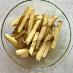 sliced potatoes with seasoning in glass bowl
