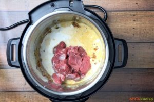 Adding coconut milk and lamb stew meat to the instant pot