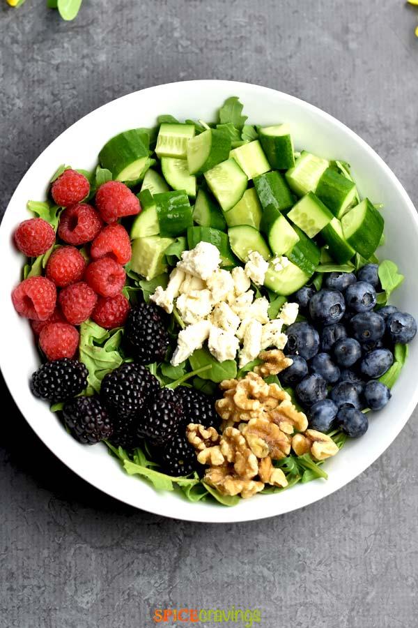arugula, cucumbers, raspberries, blueberries, blackberries, walnuts, feta in white bowl