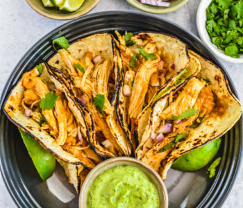 four corn tortillas filled with chicken tinga with avocao dressing on black plate with sliced lime, chopped red onion and cilantro