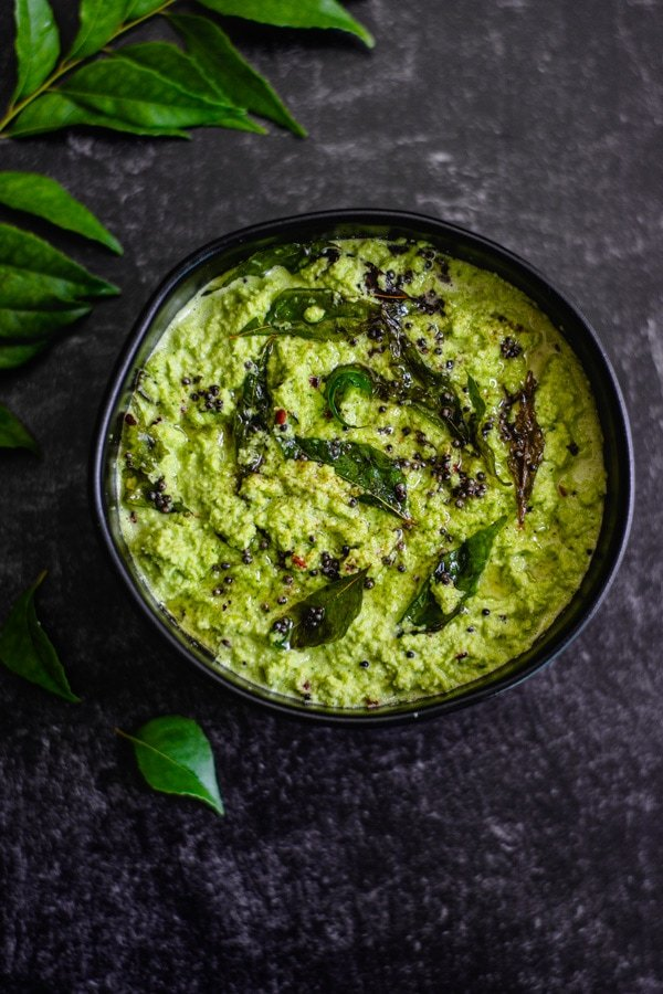 coconut chutney topped with tadka in black bowl