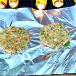 two chicken patties on aluminum foil on an outdoor grill