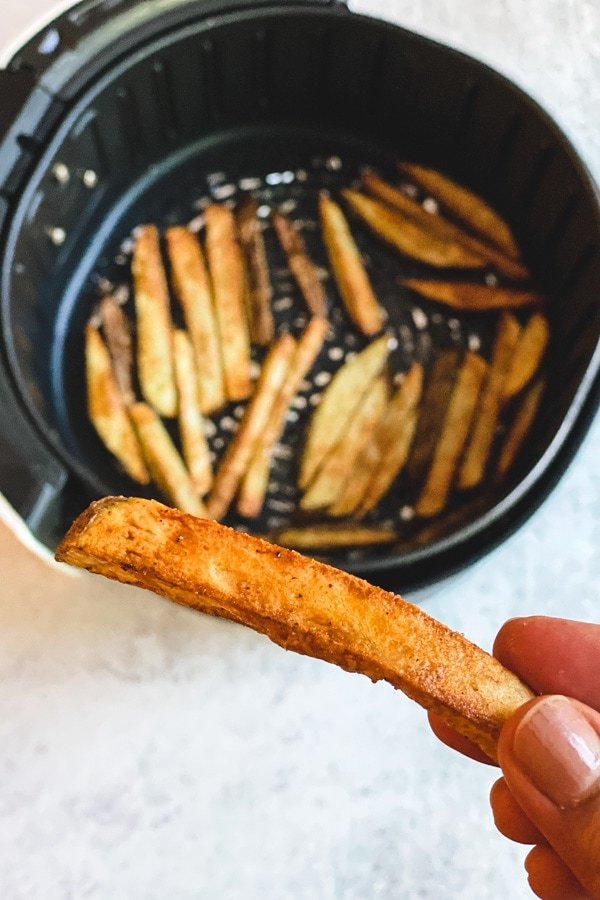 hand holding french fry over air fryer basket of fries
