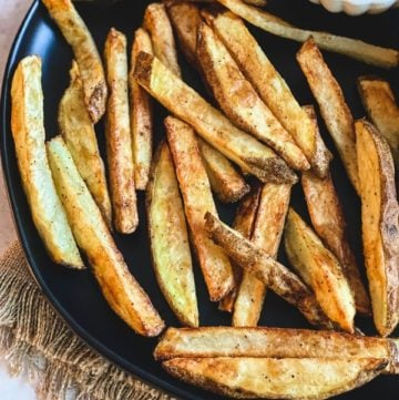homemade french fries on black plate with fry sauce in white bowl