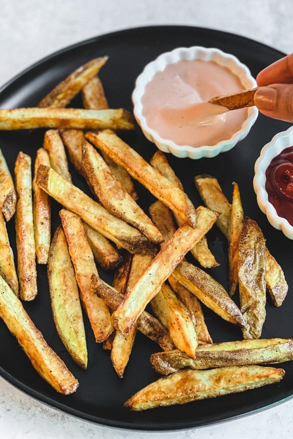 dipping fry in homemade fry sauce in white bowl with fries on black plate