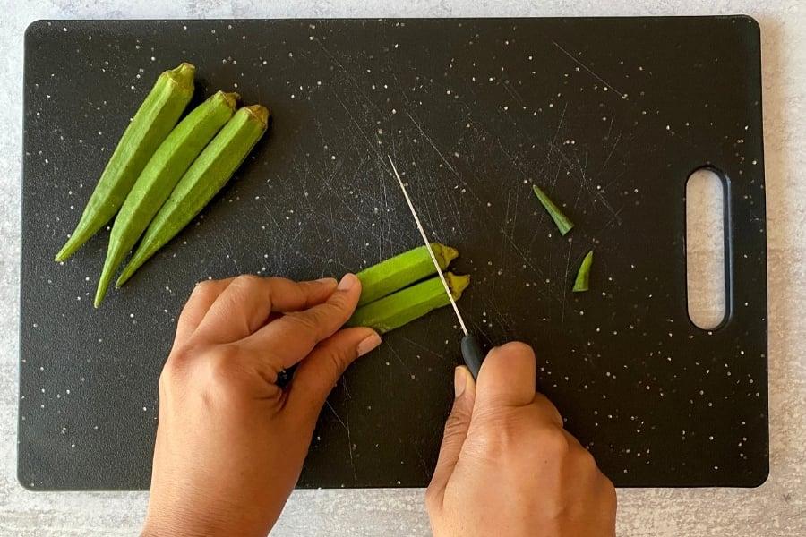 two hands cutting stems off fresh okra on black cutting board