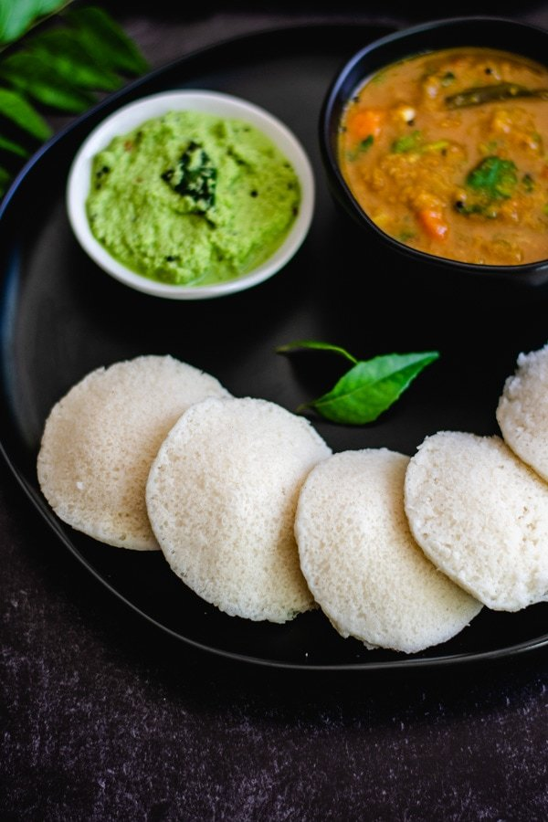 steamed idli on black plate with coconut chutney and sambar in two bowls