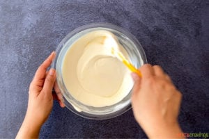 two hands stirring ice cream mix in glass bowl