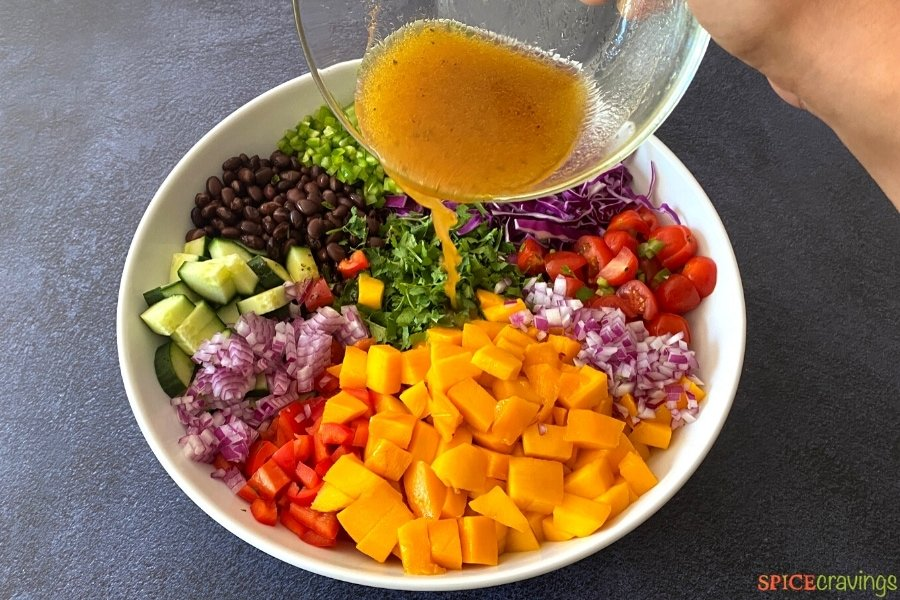 pouring lime dressing over white bowl of mango, black beans and diced vegetables