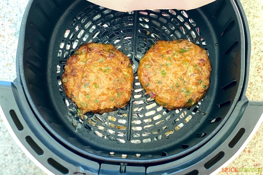 two chicken burger patties cooking in air fryer basket