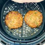 Two burger patties an an air fryer basket