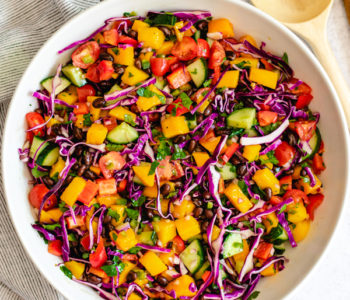 mango salad recipe with lime dressing in white bowl with wooden spoon