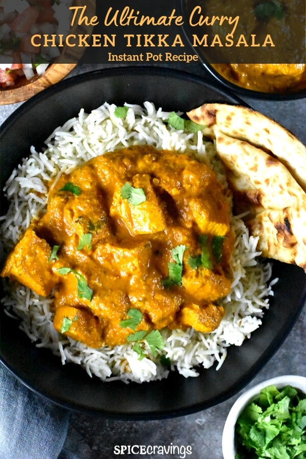 A black bowl with chicken tikka masala with rice and naan