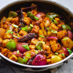 crispy chilli paneer recipe in stainless steel skillet with gray towel