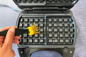 greasing waffle maker with yellow silicon brush