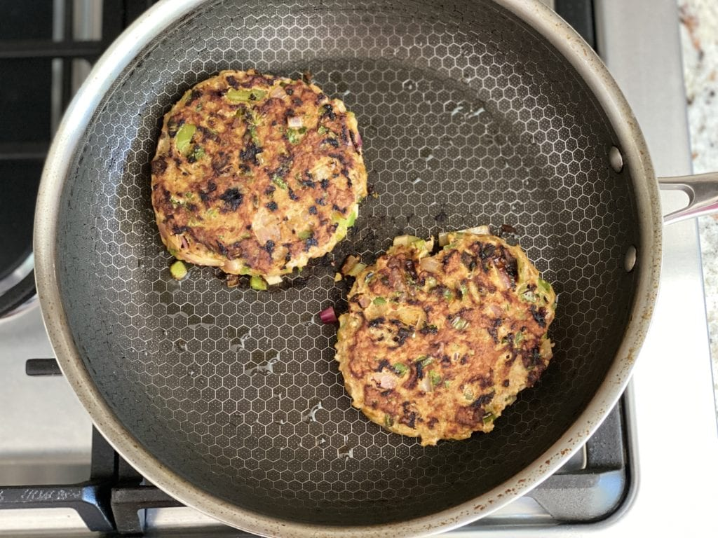 two chicken burger patties cooking in nonstick skillet