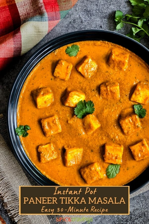 A bowl of paneer cubes in tomato sauce