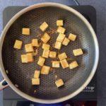 stir frying paneer cubes in nonstick skillet on hot plate