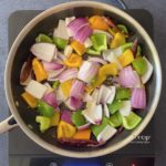 chopped onions, peppers and paneer cubes in nonstick skillet on hot plate