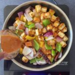 pouring Asian-style sauce into skillet with onions, peppers and paneer cubes