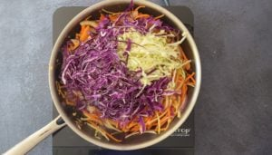 sliced cabbage and carrots in chef pan on hot plate