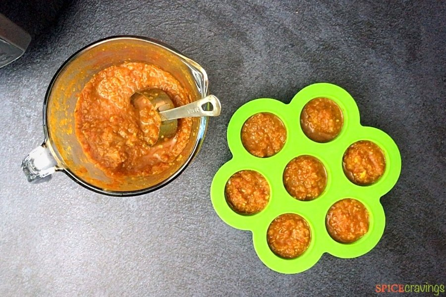 A measuring cup and silicone mold filled with Indian curry sauce