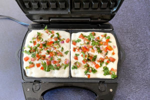 indian waffle batter topped with tomatoes, onions and cilantro in waffle maker