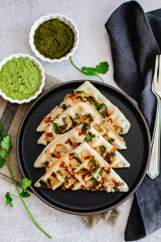 uttapam waffle recipe on black plate with two bowls of chutney on side