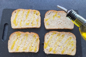 drizzling olive oil on four slices of bread