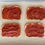 tomato sauce smeared on four slices of bread on parchment-lined baking sheet